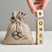 Bag of money next to blocks that spell out BONDS